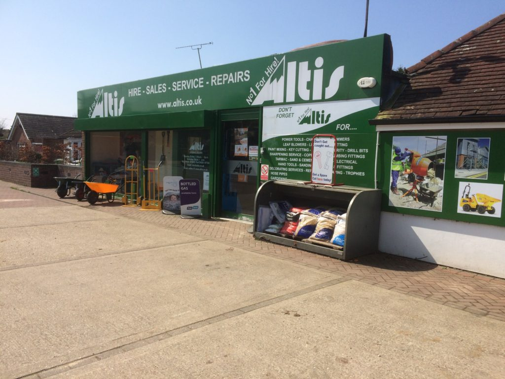 A photo of the Lindford depot of Altis Industries Ltd on Liphook Road, with a green outside and tools for hire such as wheelbarrows and cement mixers featured outside